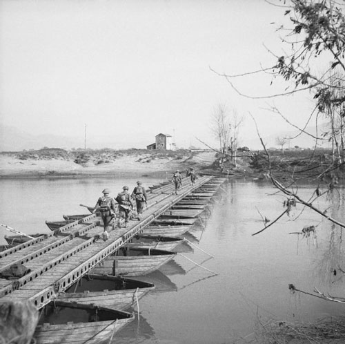 First Phase: 17 January -13 February 1944: British infantry cross a pontoon bridge over the Garigliano River at the double while in range of German artillery.